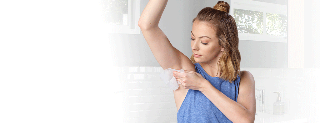 Step 2. Woman wiping QBREXZA™ (glycopyrronium) cloth over her underarm to help reduce primary axillary hyperhidrosis.